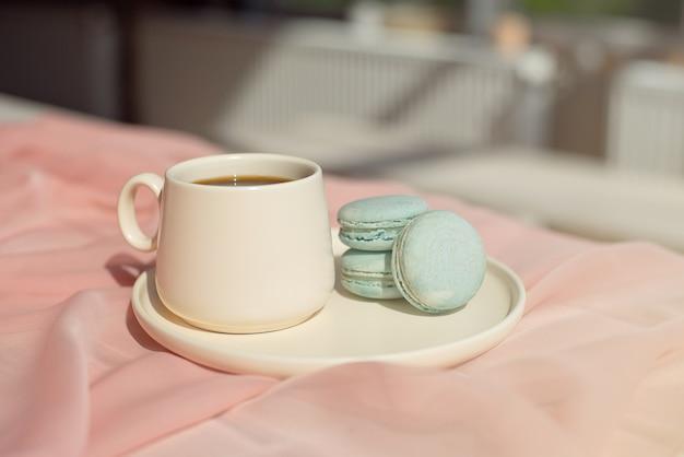 Macaron bleu français et tasse de café debout sur une table en bois avec un nappe rose vase blanc avec des fleurs roses et verts