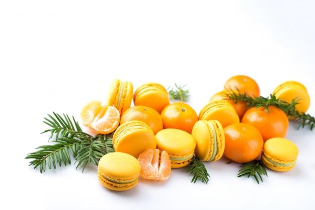 Macaron de confection se trouvent sur un fond blanc avec des mandarines et des branches d'épinette, fond pour la nouvelle année