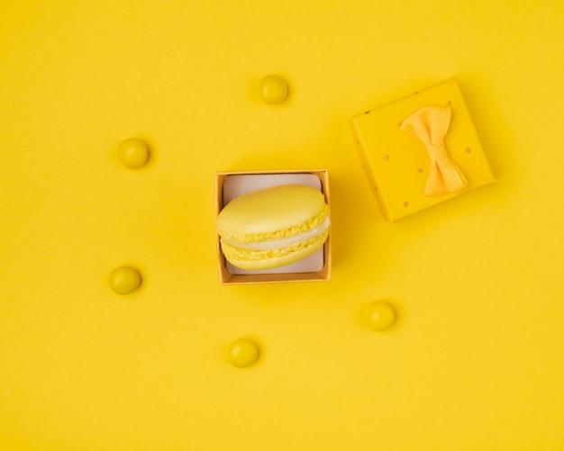 Macaron dans une boîte cadeau tout en jaune vue de dessus