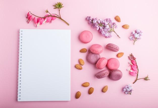 Macaron ou gâteaux macaron pourpre et rose avec carnet et fleurs lilas et cœur saignant