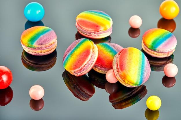 Macaron multicolore et boules de gomme à mâcher sur fond gris avec reflet.
