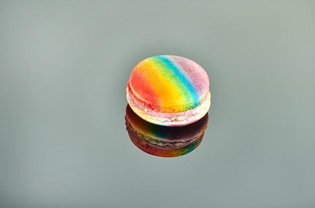 Macaron multicolore sur fond gris avec reflet.