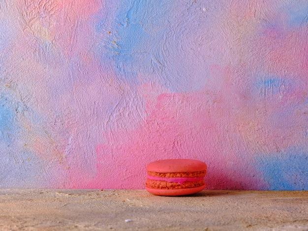 Macaron rouge sur un mur de couleur vive