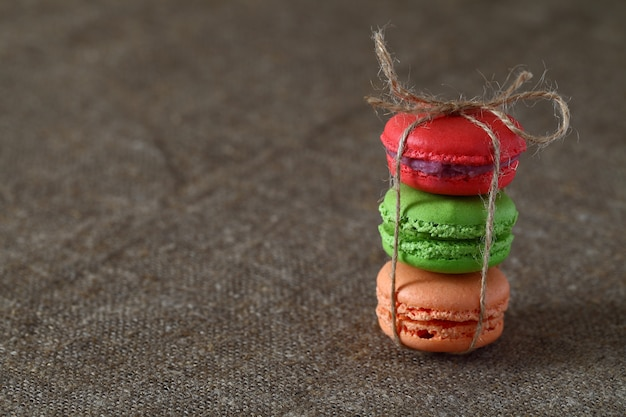 Macaron trois pièces rouge, vert et orange noué avec une corde sur une nappe en toile de jute.