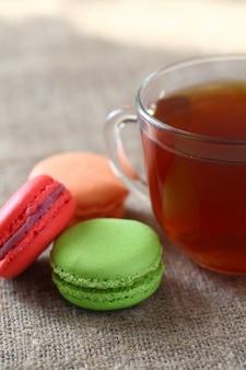 Macaron trois pièces rouge, vert et orange en vrac et une tasse de thé sur une nappe de jute. cadre vertical.