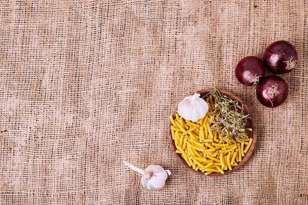Macaroni, ail et oignons sur une surface brune.