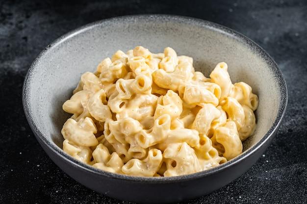 Macaroni au fromage américain avec sauce cheddar au fromage. fond noir. vue de dessus.