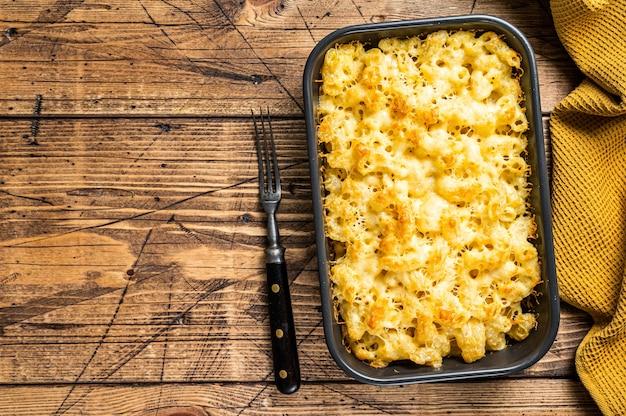 Macaroni au fromage plat américain avec sauce cheddar. fond en bois. vue de dessus. copiez l'espace.