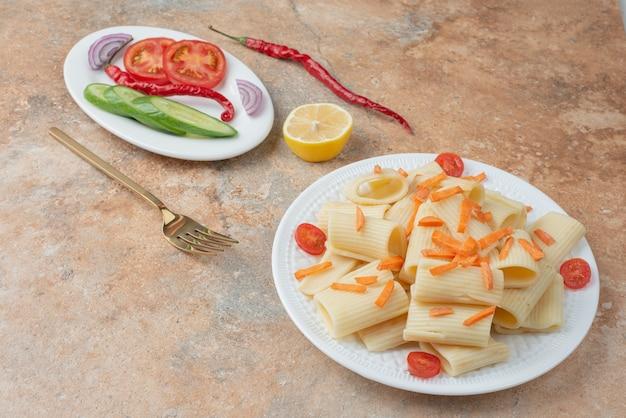 Macaroni aux carottes, tomates cerises, concombre et tranche de citron sur plaque blanche