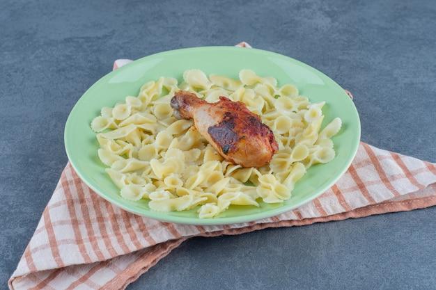 Macaroni bouilli et cuisse de poulet sur plaque verte.