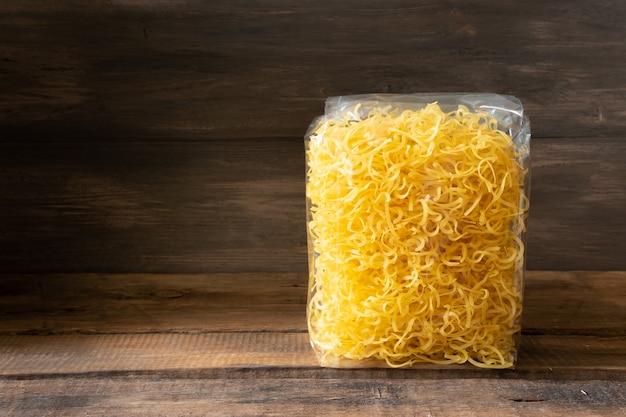 Macaroni et conserves sur un fond en bois sombre. concept de stock alimentaire
