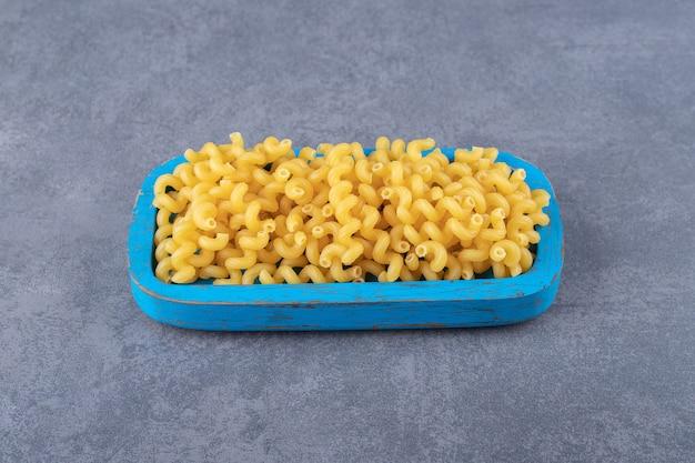 Macaroni cru de coude sur la plaque bleue.
