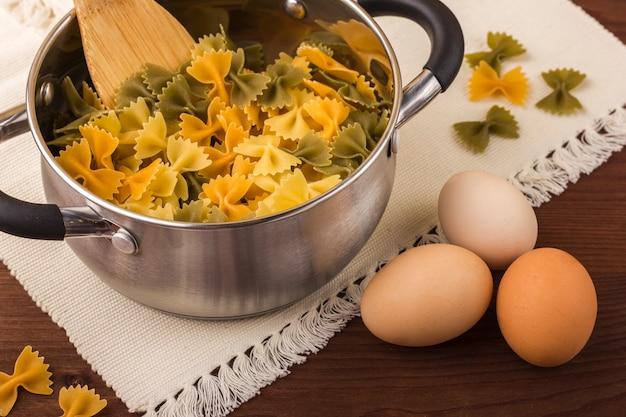 Macaroni farfalle coloré dans une casserole. trois couleurs