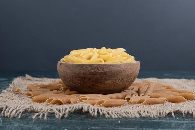 Macaroni frais non cuits sur bol en bois sur toile de jute.