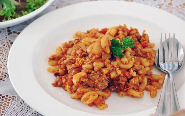 Macaroni frit avec oeuf, porc et légume à la sauce tomate dans une assiette