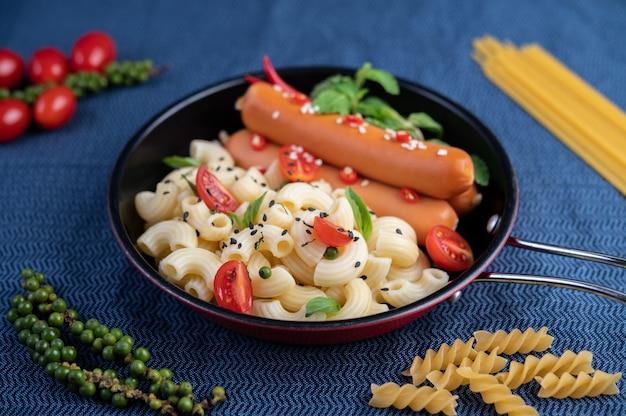 Macaroni frit et saucisse dans une poêle.