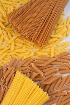 Macaroni non cuit avec des pâtes crues fraîches sur un espace blanc.