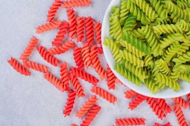 Macaroni non cuit vert et rouge sur surface blanche
