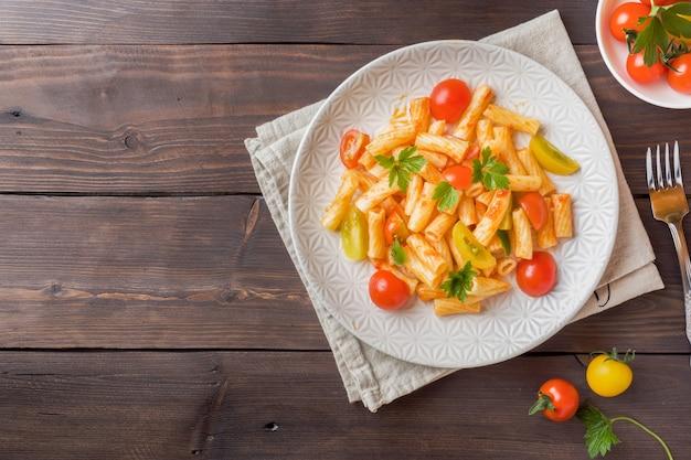 Macaroni, pâtes à la sauce tomate et fromage dans une assiette sur une table en bois