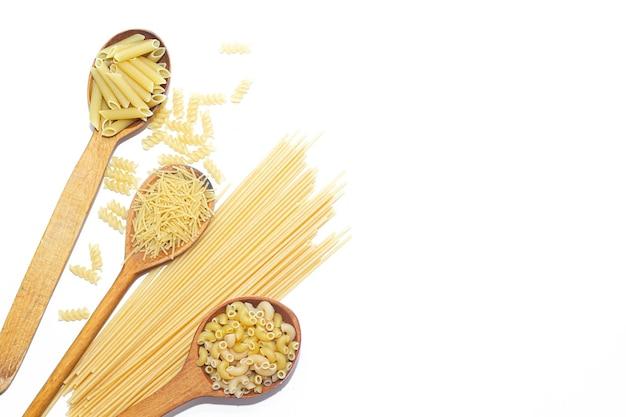 Macaroni plusieurs types dans des cuillères en bois sur blanc