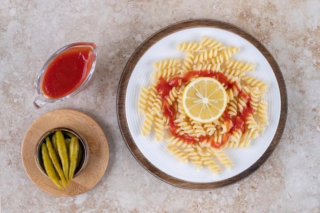 Macaroni avec portions de ketchup et poivrons marinés sur une surface en marbre.