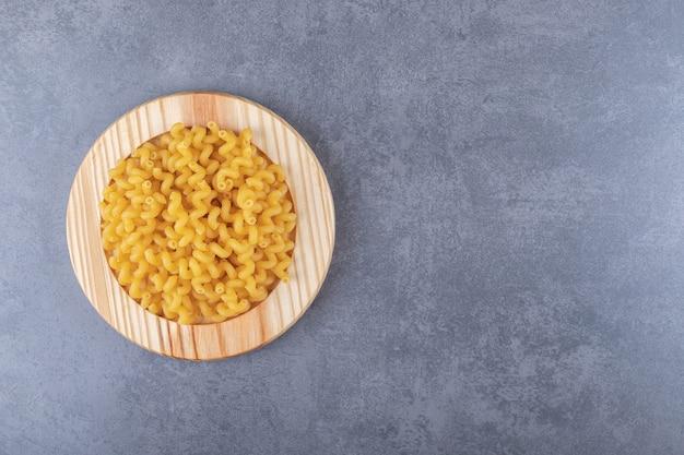 Macaroni sec cru sur plaque de bois.