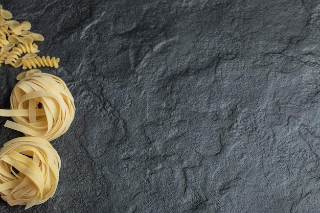Macaroni en spirale non cuit sur fond noir.