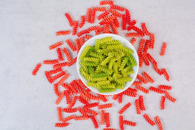 Macaronis colorés non cuits sur un espace blanc.