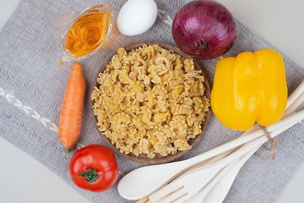 Macaronis crus aux légumes sur plaque en bois sur nappe