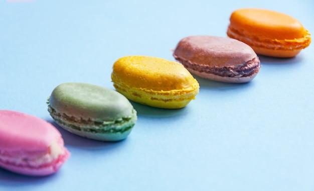 Macaronis multicolores dessert français sur fond bleu