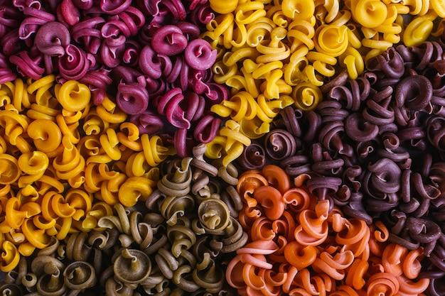 Macaronis multicolores de forme inhabituelle avec des colorants végétaux naturels, alignés dans un cercle