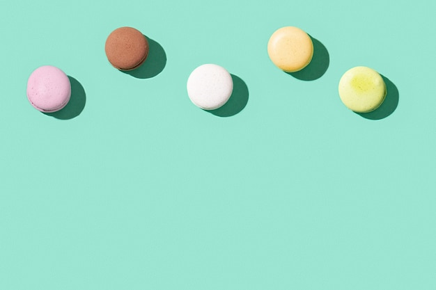 Macarons assortis sur fond de couleur vert bleu vif