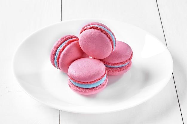 Macarons aux baies roses avec garniture crémeuse bleue sur la plaque