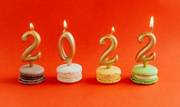 Macarons aux bougies allumées 2022 sur fond rouge. nouvelle année.