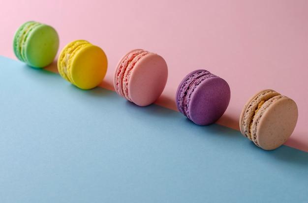 Macarons de biscuits colorés sur des couleurs pastel colorées