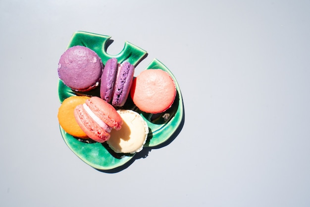 Macarons de biscuits français sur plaque de feuilles sur fond gris, vue de dessus