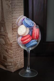 Macarons bleus et roses dans un verre.