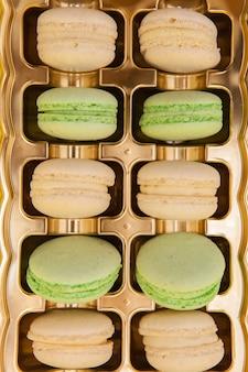 Macarons de bonbons traditionnels français dans une boîte dorée. dessert sucré