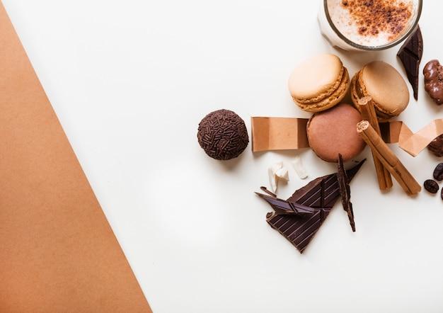 Macarons; boule de chocolat et verre de café avec des ingrédients sur fond blanc