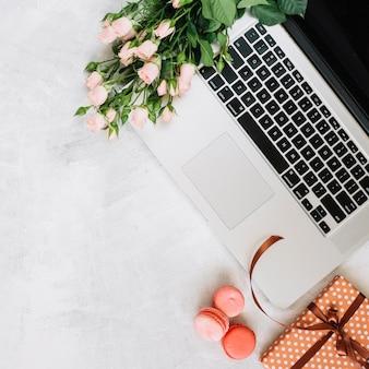 Macarons et cadeaux près de fleurs et ordinateur portable