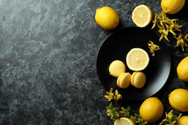 Macarons, citrons et fleurs sur fond noir fumé