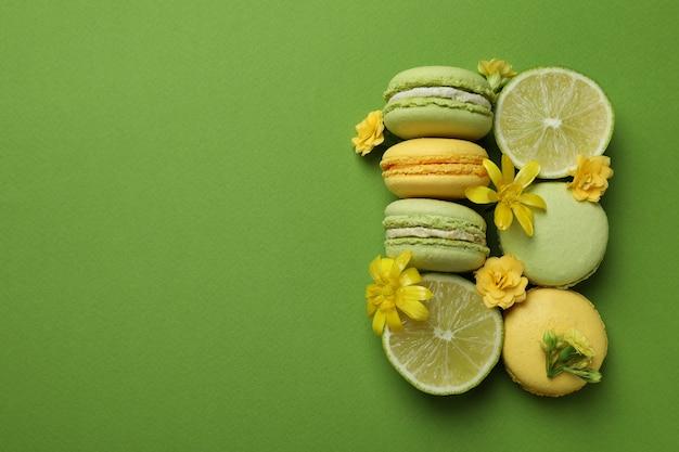 Macarons, citrons verts et fleurs sur fond vert