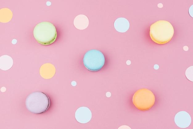 Macarons colorés arrangés avec vue de dessus de confettis