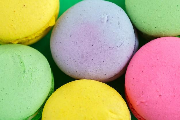 Macarons colorés ou biscuits macarons sur fond vert