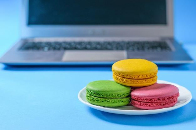 Macarons colorés dans une assiette blanche avec l'ordinateur.