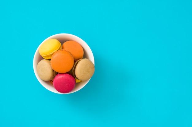 Macarons colorés dans un bol sur fond bleu copie espace