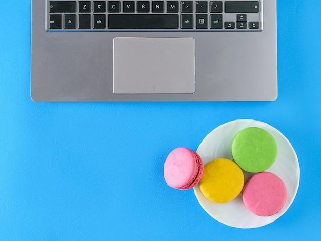 Macarons colorés dans un bol avec l'ordinateur