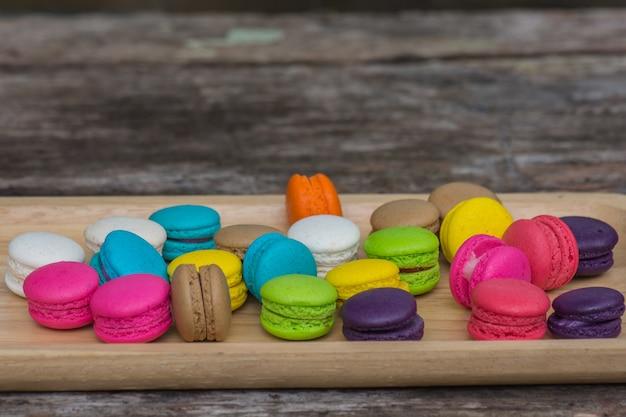 Macarons colorés dans un plat sur une table en bois