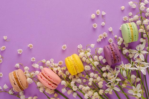 Macarons colorés décorés de fleurs de muguet sur fond violet. concept de dessert français sucré. composition du cadre. lay plat. fond concept de carte de voeux