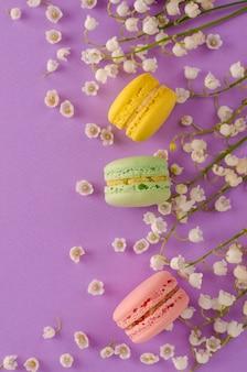 Macarons colorés décorés de fleurs de muguet sur fond violet. concept de dessert français sucré. composition du cadre. lay plat. fond verticale. concept de carte de voeux